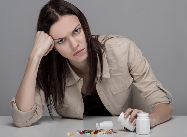 Pillen, die auf dem tisch liegen, bevor sie unter den schmerz leiden.