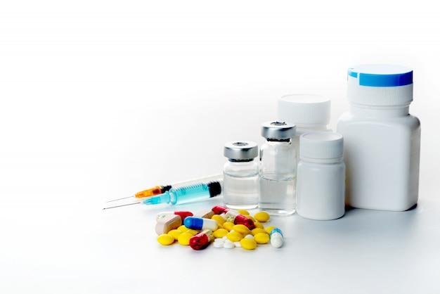 Pillen, die aus pilleflaschenspritzenthermometer und -stethoskop auf weißem hintergrund heraus verschüttet werden