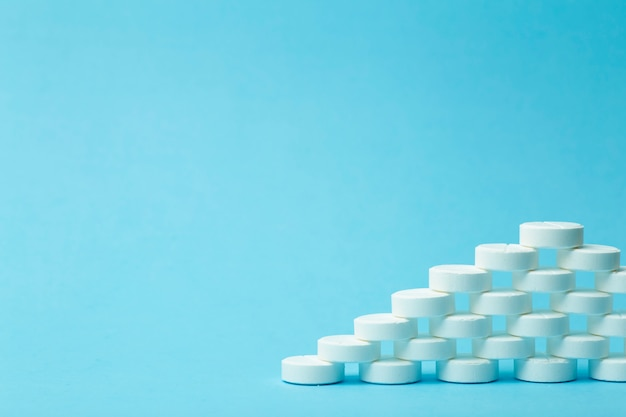 Pillen hintergrund. pillen, drags und medecine-konzept. weiße tabletten auf blauem grund