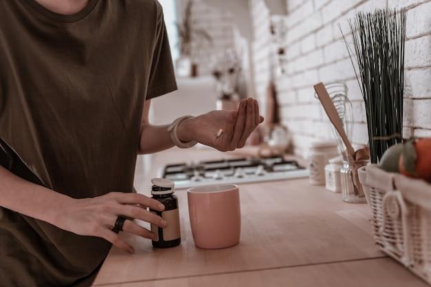 Pillen in der handfläche. junge frau im pyjama mit pillen in der handfläche in der küche stehen