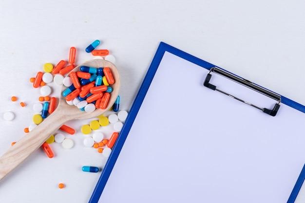 Pillen in holzlöffel mit papierhalter