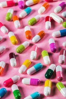 Pillen in verschiedenen farben auf einem rosa hintergrund