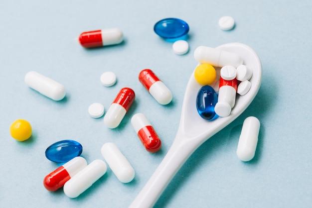 Pillen in verschiedenen farben und löffel