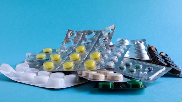 Pillen, kapseln mit medikamenten, vitamine in der packung, in blisterpackungen liegen auf dem tisch. antibiotika, mehrfarbige antibakterielle medikamente. gesundheits- und medizinkonzept. platz kopieren.