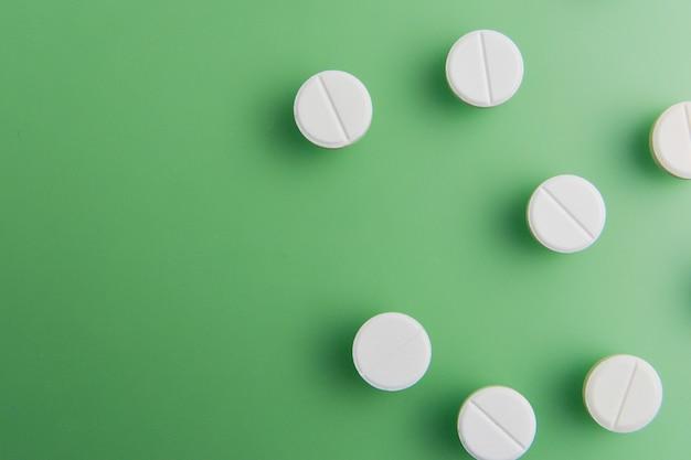 Pillen, medikamente, drogen, tabletten in weiß, auf grünem hintergrund mit tiefen schatten ausgepackt. flach liegen.