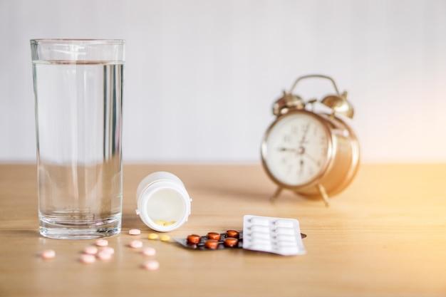 Pillen, medizinflasche, glas wasser und uhr auf holztisch