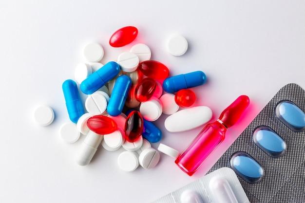 Pillen. mehrfarbige pillen. medizin. medizin. grippeinjektionen. covid 19. coronavirus-behandlung. rote und blaue pillen weiße und rote pillen. vitamine. ein berg von medikamenten. die ampulle ist rot.