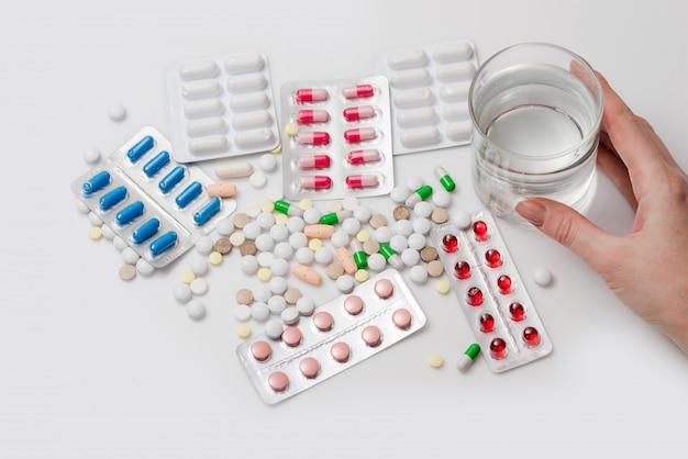 Pillen mit der hand halten glas wasser.