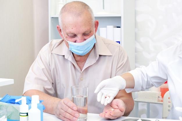 Pillen nehmen, ein glas wasser in der hand einer älteren person.