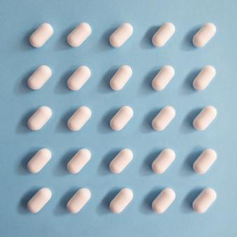 Pillen richten sich auf einem quadrat auf einem blauen hintergrund aus