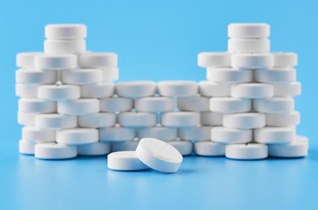 Pillen tabletten kapseln nahaufnahme. auf einem blauen hintergrund ein glas medizin.