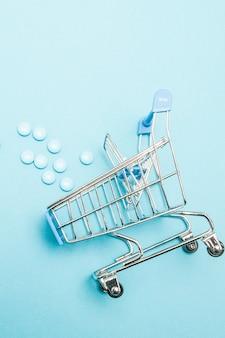Pillen und einkaufswagen auf blau. kreative idee für gesundheitskosten, drogerie, krankenversicherung und pharmaunternehmen