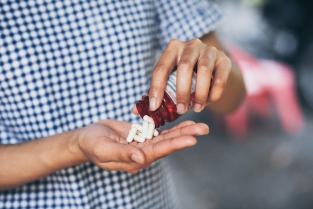 Pillen und medikamente in frauenhänden, gefährliche medikamente haben gesundheitsschädliche auswirkungen.