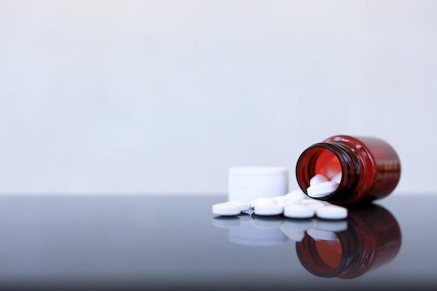 Pillen und medizinflaschen auf glas, medizinisches konzept
