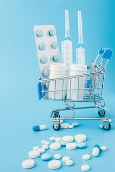 Pillen und medizinische einspritzung in der einkaufslaufkatze auf blauem hintergrund. kreative idee für gesundheitswesenkosten, drogerie, krankenversicherung und pharmaunternehmengeschäftskonzept. kopieren sie platz.