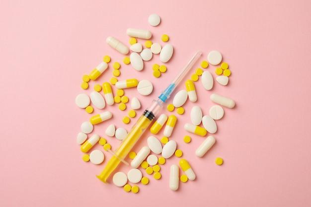 Pillen und spritze auf rosa hintergrund