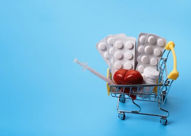 Pillen, vitamine und einwegspritze im einkaufswagen auf blauem hintergrund platz für text