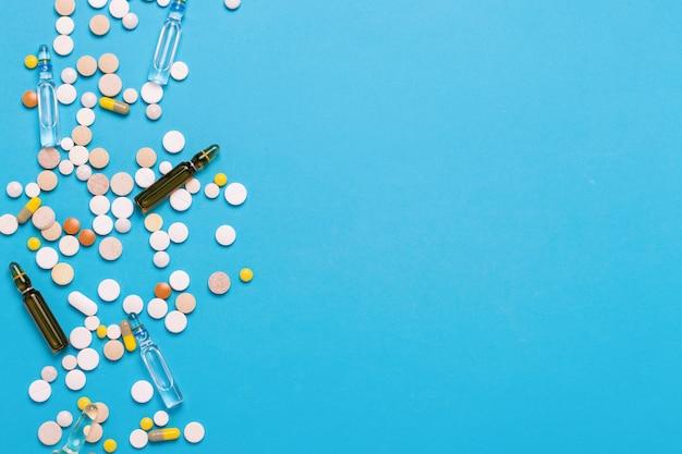 Pillen von verschiedenen farben und ampullen mit medizin auf einem blauen hintergrund. konzept der pharmaindustrie, medizin, behandlung und genesung nach krankheit. flache lage, draufsicht