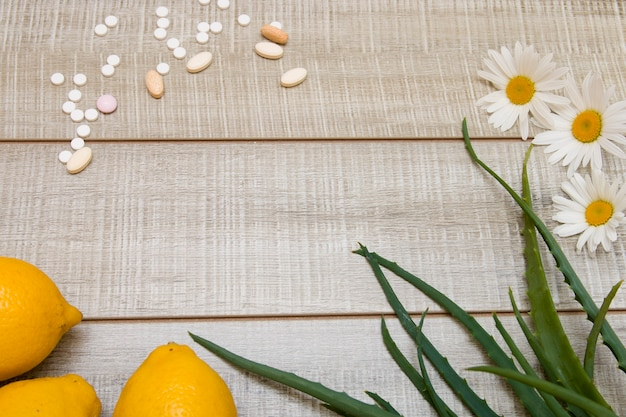 Pillen, zitronen, gänseblümchen und aloe-blätter auf einem hölzernen hintergrund