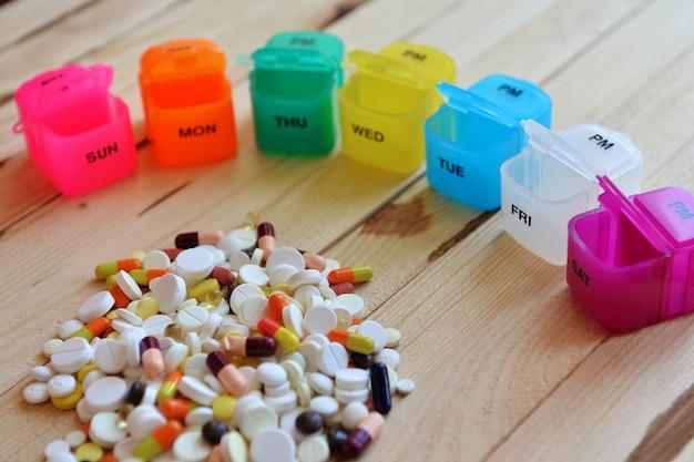 Pillenbox mit verschiedenen pillen und ergänzungen. eine wöchentliche plastikpillenbox. tägliche pillendose mit medikamenten und nahrungsergänzungsmitteln.