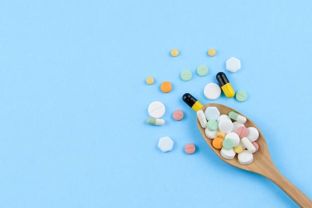 Pillentablette, -kapsel und im hölzernen löffel auf blauem hintergrund-, medizin- und drogenkonzept