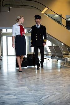 Pilot und stewardess gehen mit ihren trolley-taschen