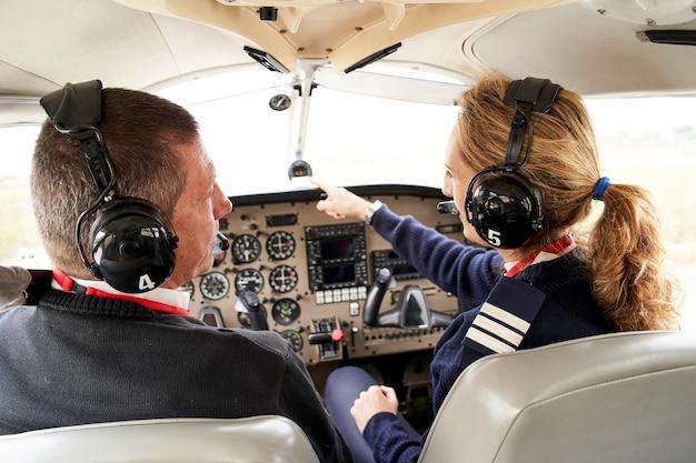 Pilotenlehrling und fluglehrerin im cockpit. die ausbilderin gibt ihrem schüler anweisungen.