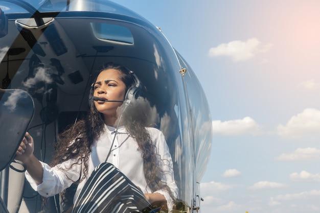 Pilotin im cockpit des hubschraubers vor dem start. junge frau hubschrauberpilot.