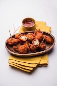 Pilz 65, vorspeise oder vorspeise essensrezept aus indien. auf einem teller mit ketchup serviert. selektiver fokus