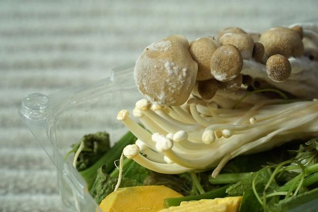 Pilz auf pilz mit gemüse in plastikbox mischen