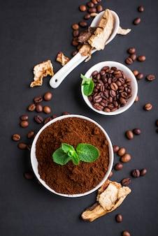 Pilz chaga kaffee superfood trend-trockene und frische pilze und kaffeebohnen auf dunkler oberfläche mit minze. kaffeepause