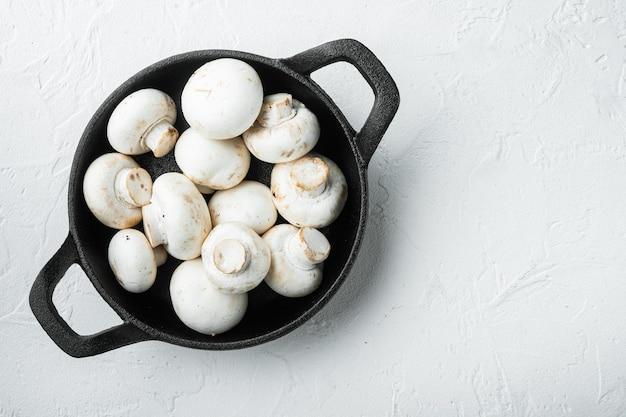 Pilz-champignon-set, in gusseiserner pfanne, auf weißer steinoberfläche, draufsicht flach gelegt