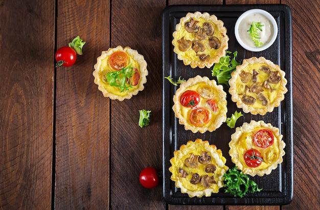 Pilze, cheddar, tomatentörtchen auf hölzernem