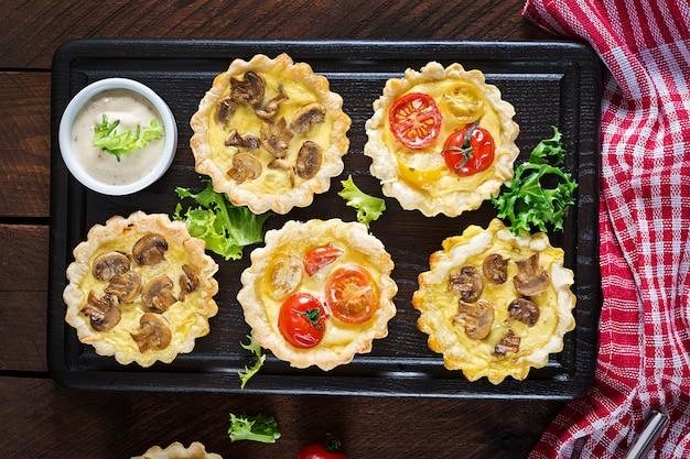 Pilze, cheddar, tomatentörtchen auf holz