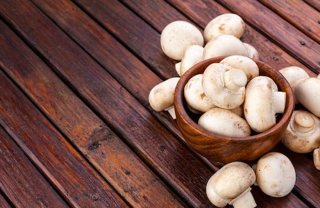 Pilze in der schüssel auf hölzernem, kopienraum.