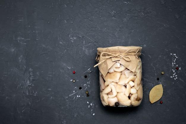 Pilze in einem glas auf einer schwarzen wand mit kopierraum, draufsicht. das konzept der hausgemachten rohlinge. platz für ihren text.
