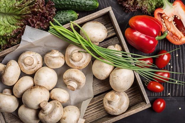 Pilze in einer holzkiste und gemüse.