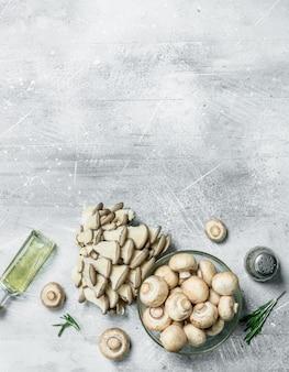 Pilze in einer schüssel und ein bündel austernpilze mit öl und pfeffer. auf rustikalem tisch