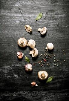 Pilze mit gewürzen. auf einem schwarzen rustikalen hintergrund.