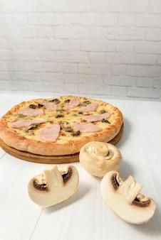 Pilze und pizza mit schinken und pilzen auf einem hellen hintergrund mit kopienraum.