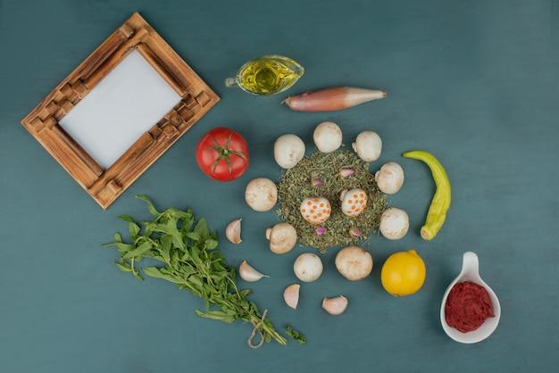Pilze, zitrone, pfeffer, minze, tomate und öl auf blauem tisch mit bilderrahmen.