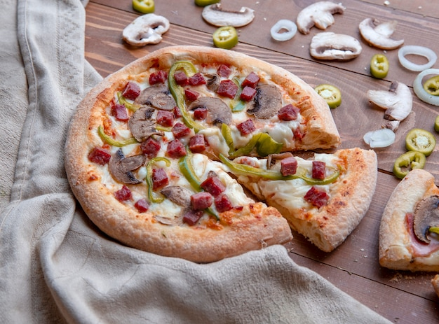 Pilzpizza geschnitten auf dem holztisch