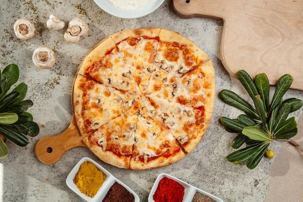 Pilzpizza mit pilzen und gewürzen auf dem tisch