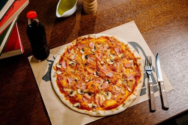 Pilzpizza mit zusätzlichem mozzarella-käse und kräutern auf einem holztisch, draufsicht