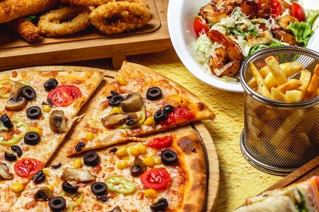Pilzpizza von der seite mit tomaten-schwarzoliven-käse mit pommes frites und caesar-salat mit gegrillten garnelen auf dem tisch