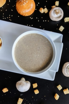 Pilzsuppe in der schüssel cracker brötchen sesam draufsicht