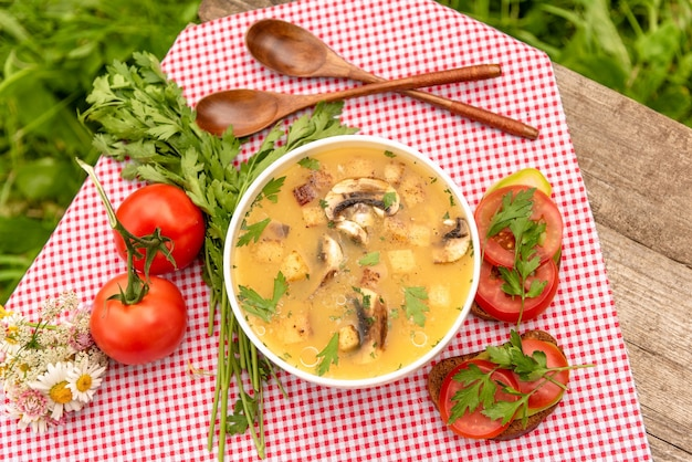 Pilzsuppe mit croutons und gemüse an der frischen luft.