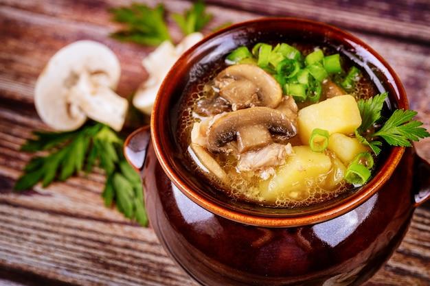 Pilzsuppe mit kartoffeln und schnittlauch in einem tontopf
