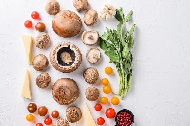 Pilzzutaten zum backen von portobello, cheddar-käse, kirschtomaten und salbei auf weißem hintergrund draufsichtraum für text.