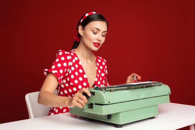 Pin herauf das mädchen, das auf einer schreibmaschine schreibt